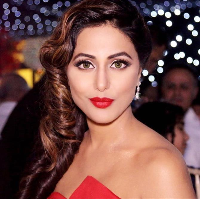 Hina Khan is seen keeping her hair on one side and flaunting her curvy brownish hair along with red lips and red outfit.