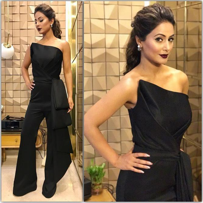 Hina Khan is seen wearing a black jumpsuit and her brownish hair ponytail with dark brown lips.