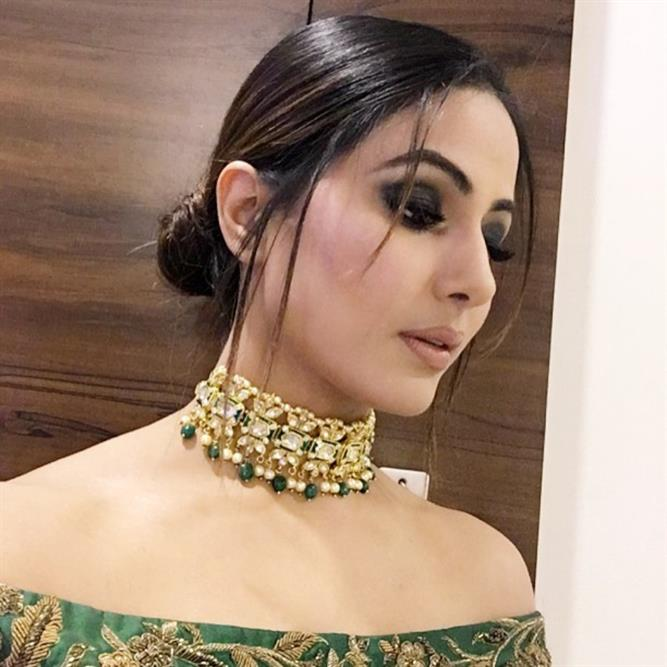 Hina Khan is sporting a stylish messy bun with strands of hair and her black eye makeup just completes the look.
