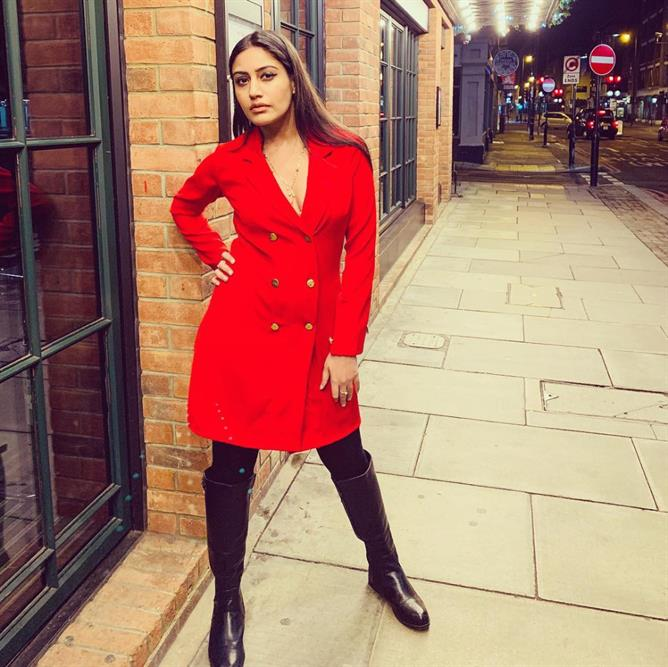 Red Alert Surbhi Chandna in a red tuxedo dress also wearing black boots to complete her look.