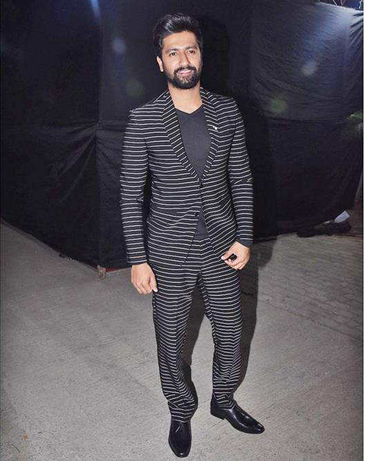 Vicky Kaushal is seen wearing a black striped suit