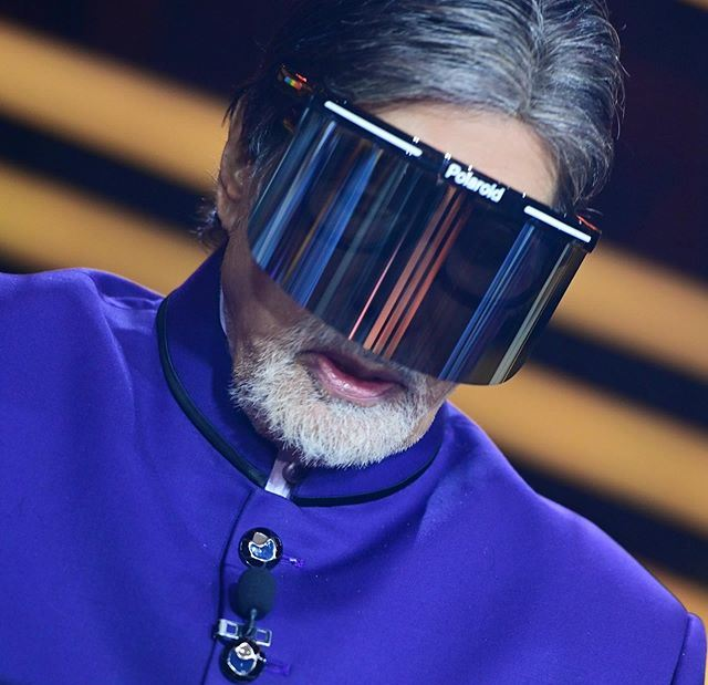 Amitabh Bachchan covers his face with a Polaroid
