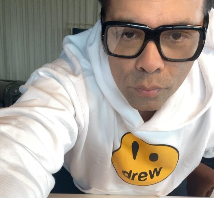 Karan Johar with large spectacles and white tee in an instagram post