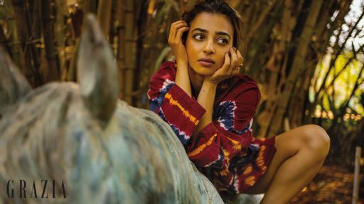 Radhika Apte in a tie-dye maroon jacket with a white tube top and red-white striped shorts